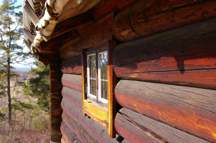 Timmervägg som blekts av solen. Fönster med blyspröjs och näver som sticker fram under taket